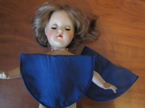 Turning a discarded shoulder pad into a blouse for the doll.