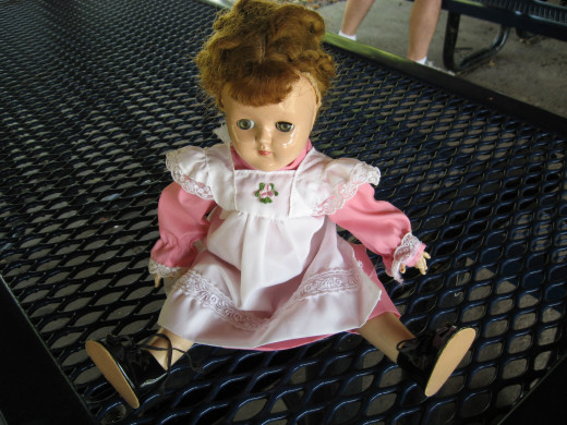 My sister's doll wearing a typical dress with a white pinafore.