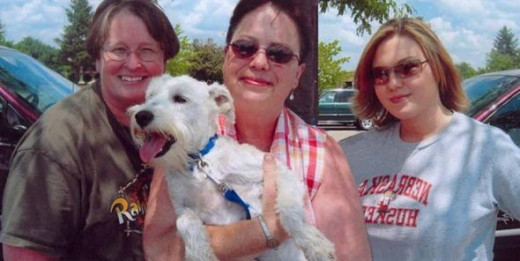 In this photo, left to right are volunteer and major donor Sheryl, Scamp the Schnauzer on his way to a new home, me, and my daughter Cari.