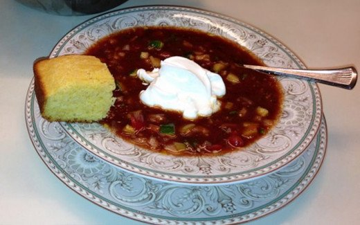 My delicious gazpacho soup with garnishes of light sour cream and homemade cornbread, prepared and photographed by Margaret Schindel