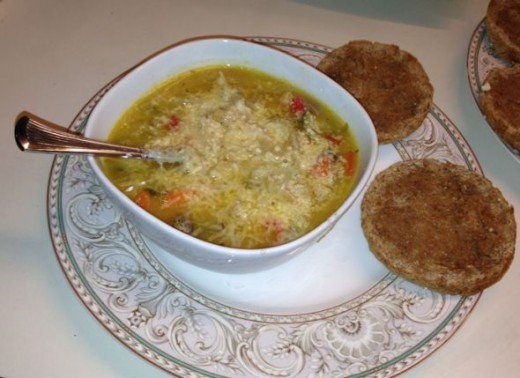 Vegetable soup with cannellini beans and chicken sausage, garnished with finely shredded fresh Parmesan cheese and served with whole-grain English muffins.