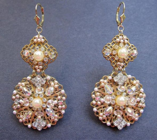"Earrings made with brass filigrees encrusted with pearls, rhinestones, Swarovski crystals, seed pearls, and pearl and crystal components from broken vintage bracelets using fine wire as embroidery ""thread."" A custom commission."