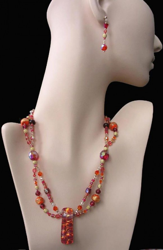 This two-strand necklace with a dichroic art class focal pendant and matching earrings combine rare vintage glass and metal beads with contemporary glass and crystal beads in a summery palette of pinks and oranges in a gorgeous mix of hues.