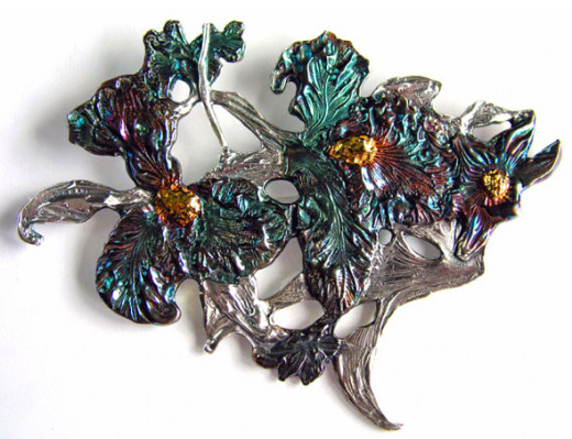 Large fine silver iris brooch I made with precious metal clay. The iridescent colors on the petals are a liver of sulfur patina; centers are 24k gold.