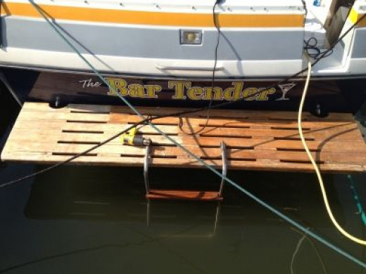 The before photo - This teak swim platform needed to have the old wood finish sanded off