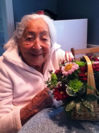 A happy 94 year old with a basket full of garden flowers