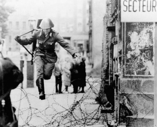 East German Soldier jumping to freedom while dropping his gun.