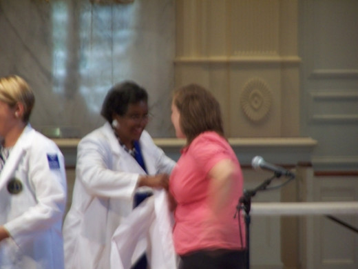 Receiving her coat from instructor, Marquitha Mayfield, M.Ed., PA-C
