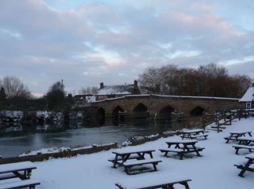Newbridge where the River Windrush meets the River Thames winter snow cover the Maybush Inn garden