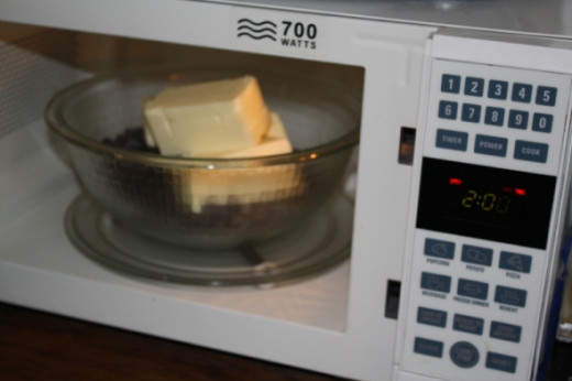 When melting in the microwave, put the butter on top because it melts faster than the chocolate; take it out at 2 minutes and mix.  When melting on the stovetop, put the butter in first for the same reason.