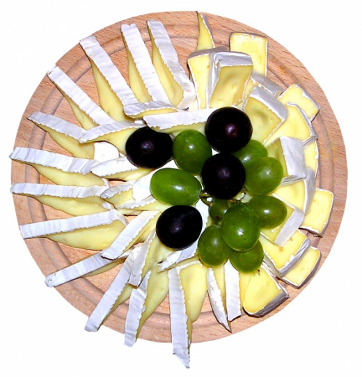 Camembert Cheese and Grapes decoratively arranged on a Wooden Platter