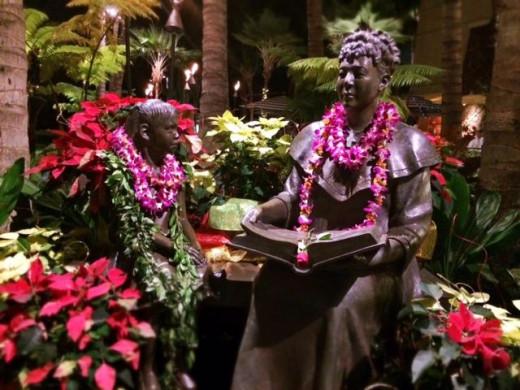 Hawaiian statues decorated with holiday joy.