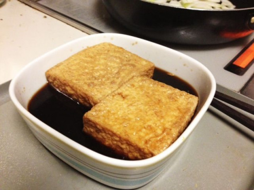 Marinate the tofu in soy sauce mixture. I've used deep-fried tofu for this recipe, but firm tofu works perfectly.