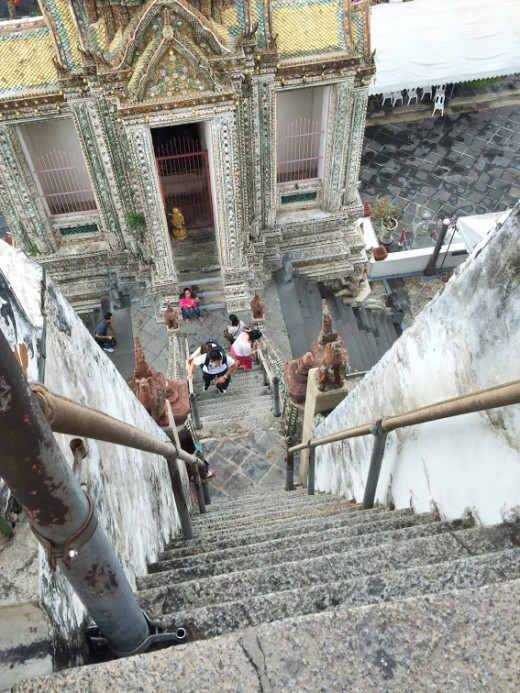 Climbing the perilously steep stairs up Wat Arun.