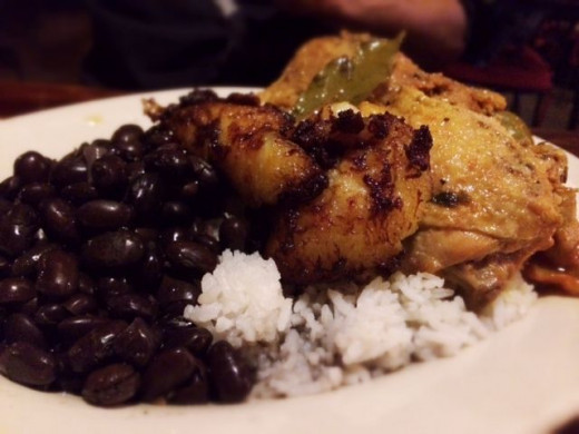 Fricase de Pollo, marinated chicken sauteed with onions and spanish olives, served over arroz blanco with frijoles negros and platanos maduros.