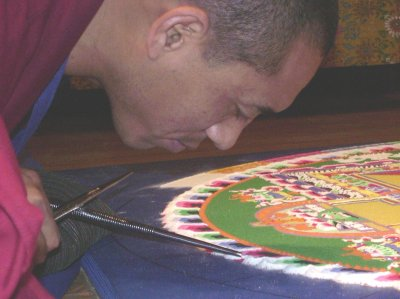 Tiny grains of colored sand sift through tubes to construct the sand mandala