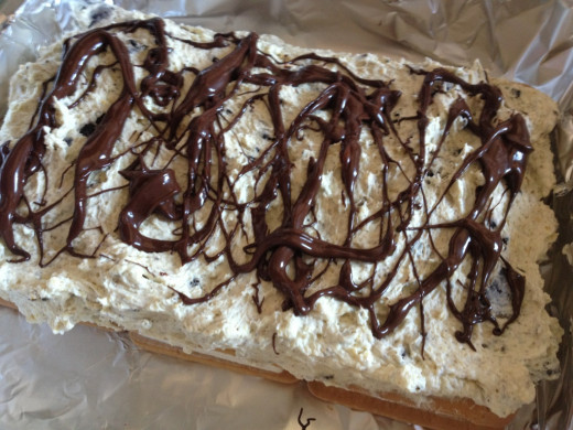Frost the entire cake with the remaining whipped cream mixture and drizzle with chocolate syrup.