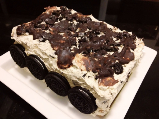 Add crushed oreos, additional chocolate syrup and whole oreos to decorate the cake. Freeze until ready to eat.