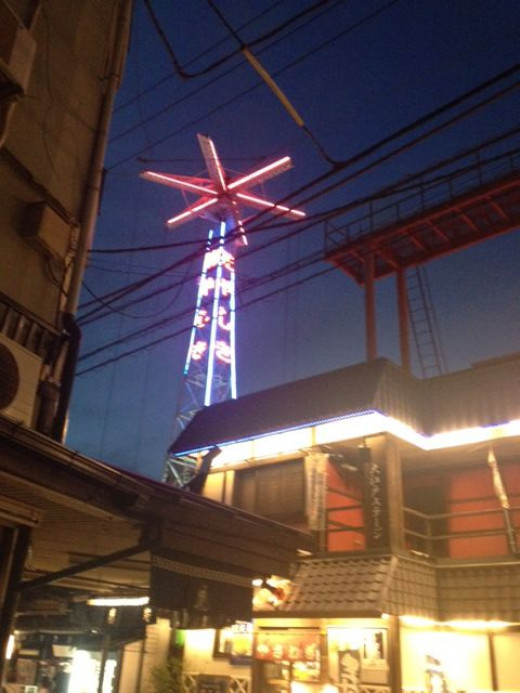 The towers of the oldest amusement park in Japan sits near the temple grounds.