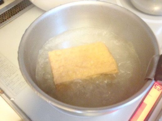 Boil the aburaage in boiling water for 1 minute to remove excess oil.
