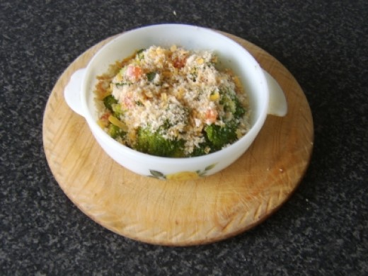 The cheese crumble is scattered over the cooked broccoli