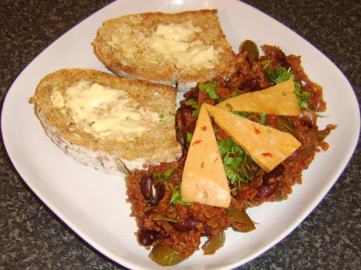Spicy beef and bean chili is served with spicy Mexican cheese and toasted wheat, spelt and rye bread