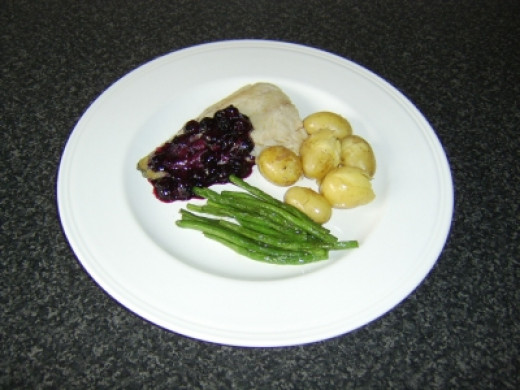 Coley fillet is simply grilled (broiled) and served with a sauce made from blueberiies and red wine
