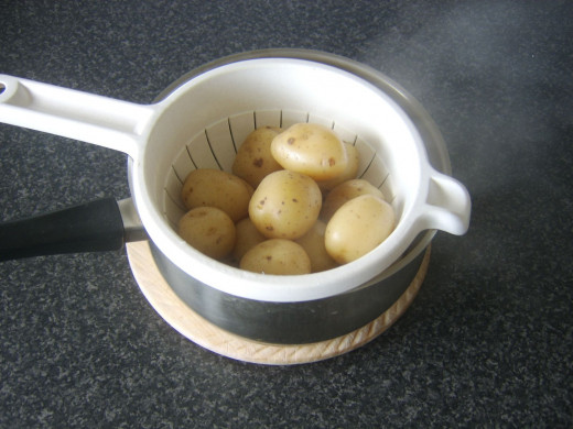 Boiled potatoes are drained and allowed to steam