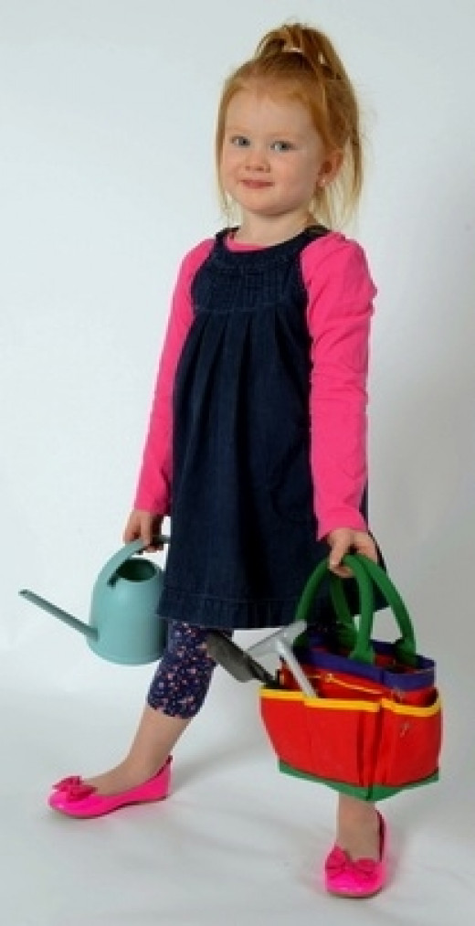 A happy gardener toting her kid-sized Garden Kit and watering can.