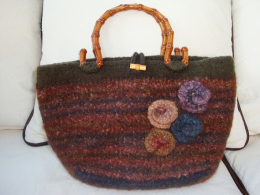 Earth tones make this felted purse look fashionable in the fall and summer. The bamboo handles and felted flowers from leftover yarn add a special touch.