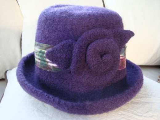 Solid purple wool yarn was used to create this felted hat. A ribbon and a rosette embellished this felted hat.