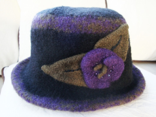 Black and purple yarn were combined to create contrasting borders to this hat. Leaves and a beaded flower were added to add some pizazz.