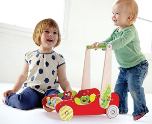 Hape Eco Push and Walk Activity Wagon - Brightly colored red push cart to fill with favorite toys and carry around the house. Little girls can pretend to take their baby doll toy for a walk just like mom. Handles have a cute blue and orange worm pain