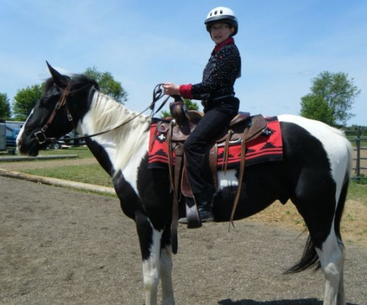 The red saddle blanket on this black and white horse goes with the black show shirt with red trim on the collar and wrists.
