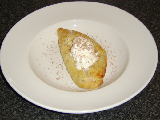Apple Turnover with Whipped Cream and Chocolate Dusting