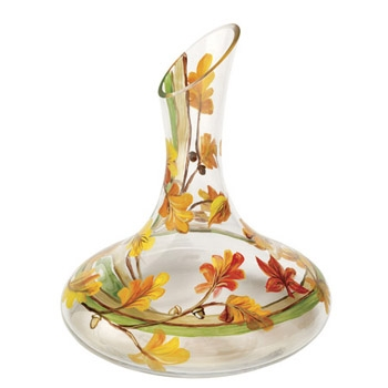 """Give a toast to the arrival of fall with the Fall Leaves Wine Glass Decanter! Wrapped around the glass is a hand-painted, wistful autumn scene of auburn, marigold, and saffron colored leaves and hip kiwi and capuccino stripes. At 11"""" tall and 8"""" diam"""