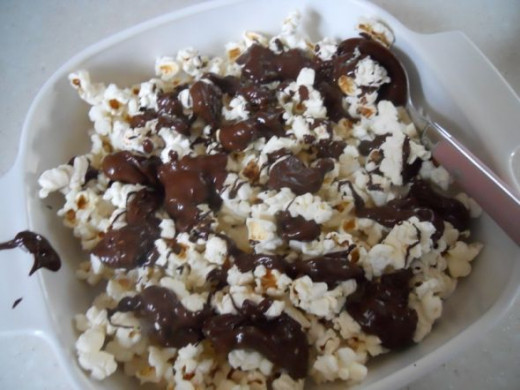 Spoon melted chocolate over popcorn.