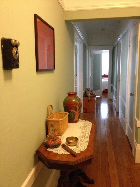 Our hallway after its mini makeover, with the lovely vase now given a place of prominence on the table, and near the framed art paper whose warm reds and golds it echoes
