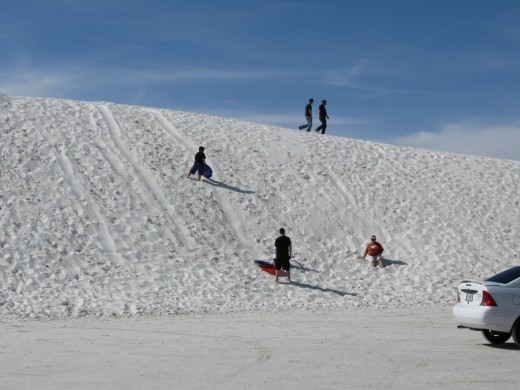 Sledding on a dune in White Sands National Monument, New Mexico