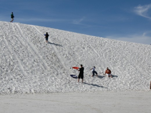 Families sledding on the sand dune at White Sands National Monument in New Mexico.