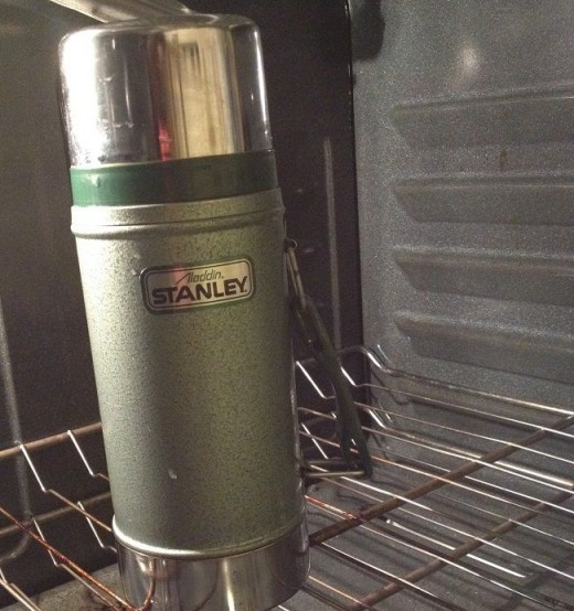The thermos filled with inoculated milk, resting for 8-12 hours in the oven with the light turned on for added warmth