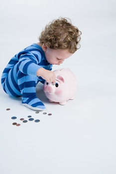 Boy Putting Coins Into His Piggy Bank