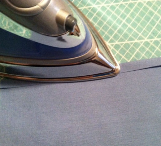 Cut out a square of cloth about 1 and 1/2 inches wider and longer than you want the finished napkin to be. With the wrong side up,  fold over 1/4 inch of fabric. Iron to hold it in place.