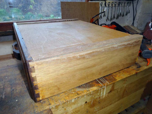 Thin strips of plywood are cut and glued into place to replace the worn drawer bottom sides.