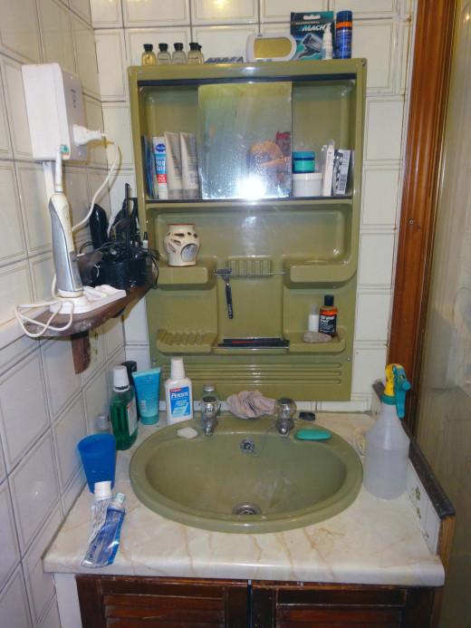 The original old tatty plastic bathroom cabinet, wash basin and under sink cupboard.