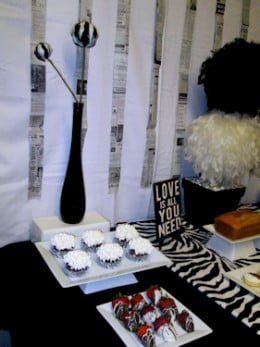 Left side - black bottle w/ black & white striped feather ball stem on riser, pedestal platter with cupcakes, flat square platter with strawberries