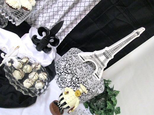 Middle Right - truffles platter on a riser covered in black fabric and the fleur de lis on white satin & the jolly chef, & Eiffel Tower.