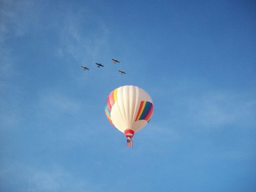 Hot air balloon soaring across the sky with American flag while jet planes flyover