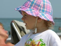Baby on beach wearing a hat