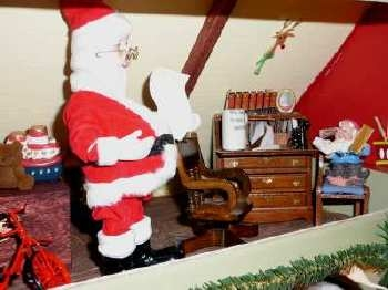 Oh ! Here's Santa hard at work in his workshop... Looks like an elf helps him answer his many letters.